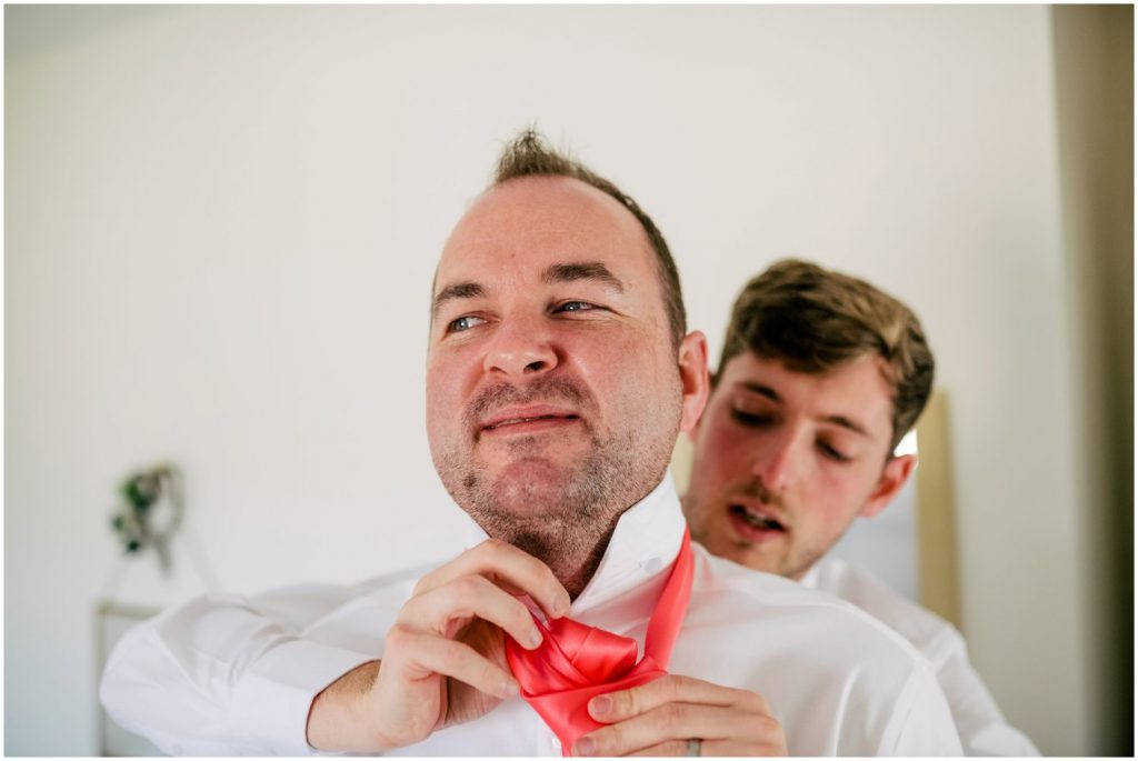 groom and bestman putting on ties