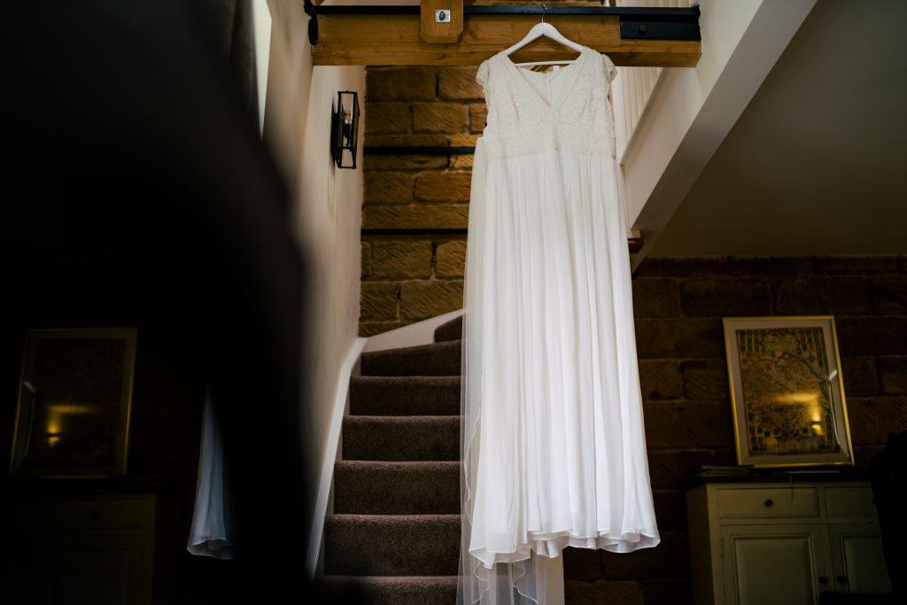 Wedding dress hanging in window light
