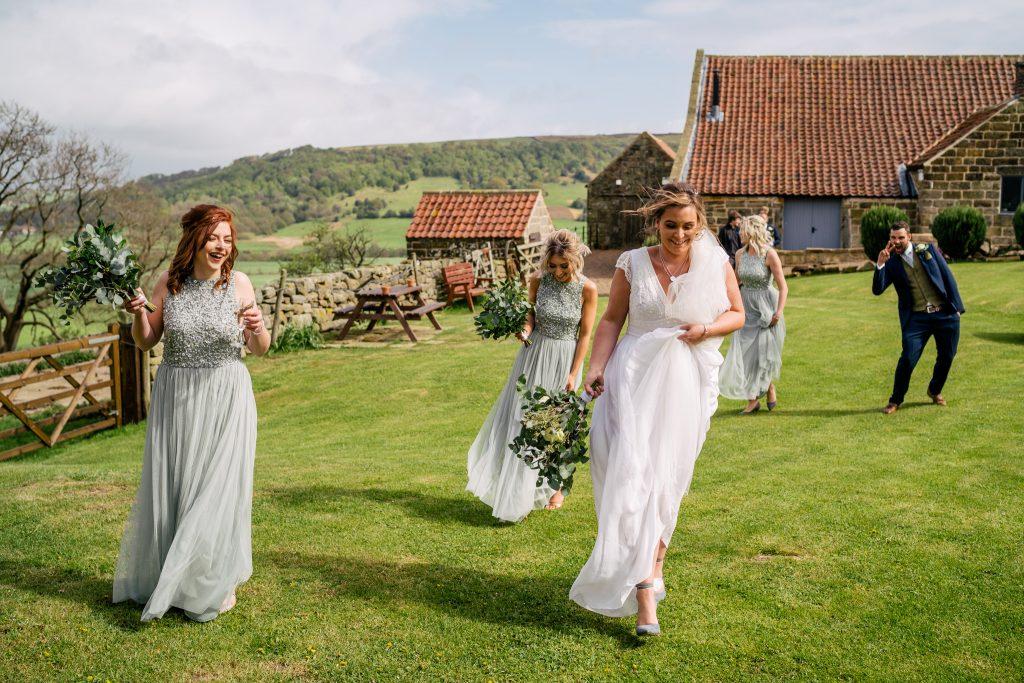 Bridal party walking across Danby Castle