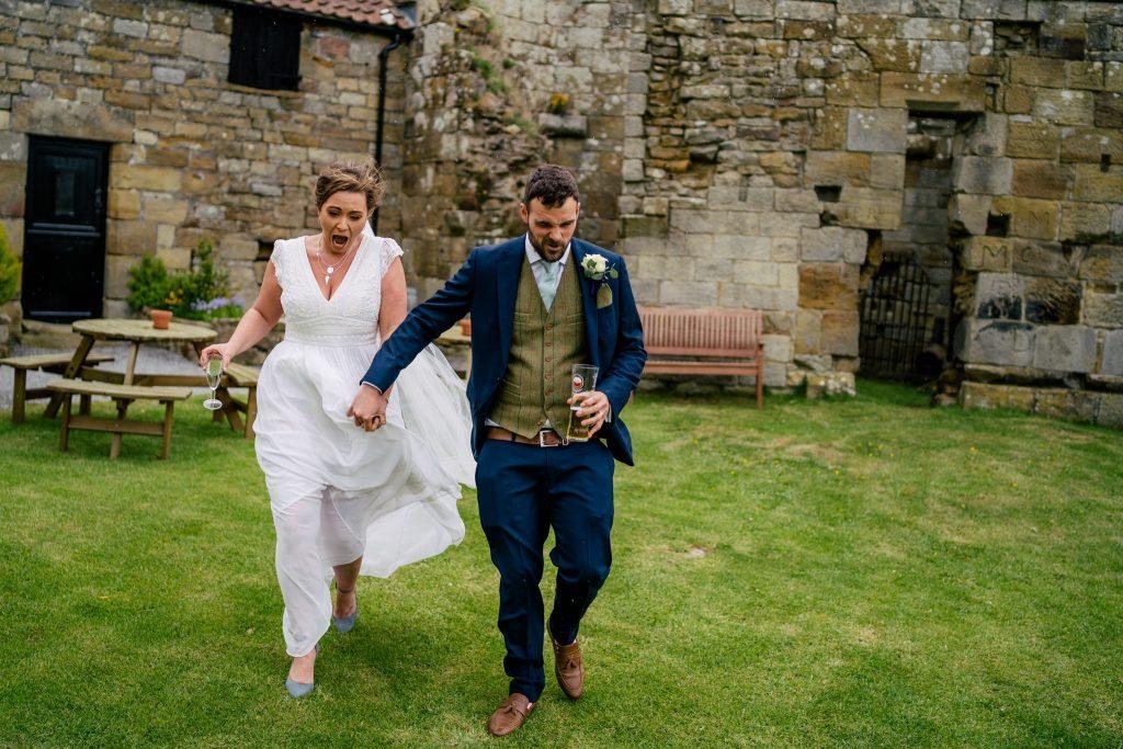 Bride and Groom running across Danby Castle