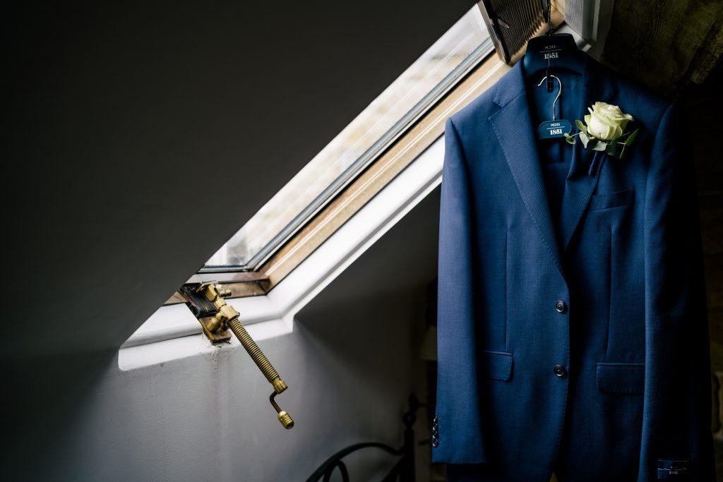 Grooms suit hanging in window